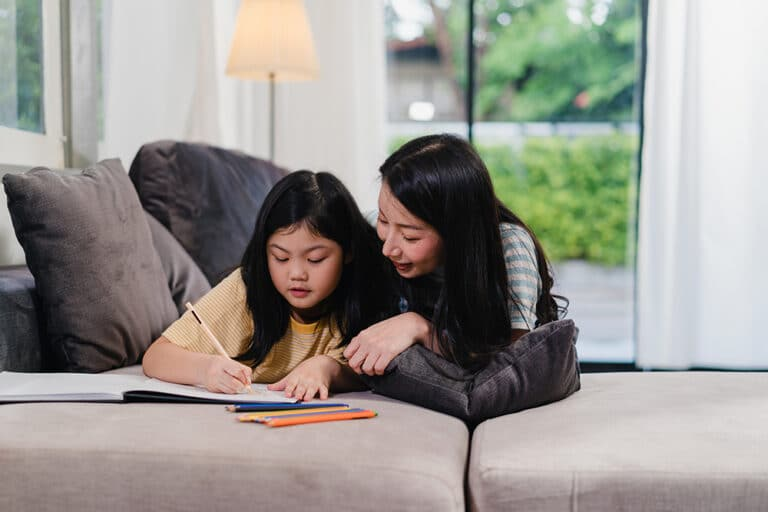 Asian middle-aged woman teach her daughter do homework and drawing at home. Lifestyle mother and kid happy fun spend time together in living room in modern home in the evening concept.