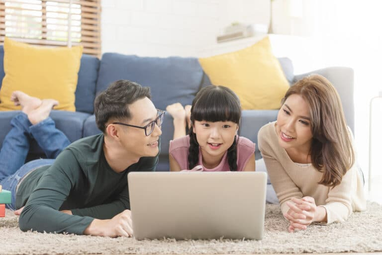 Happy Asian family using computer laptop together on sofa at home living room.