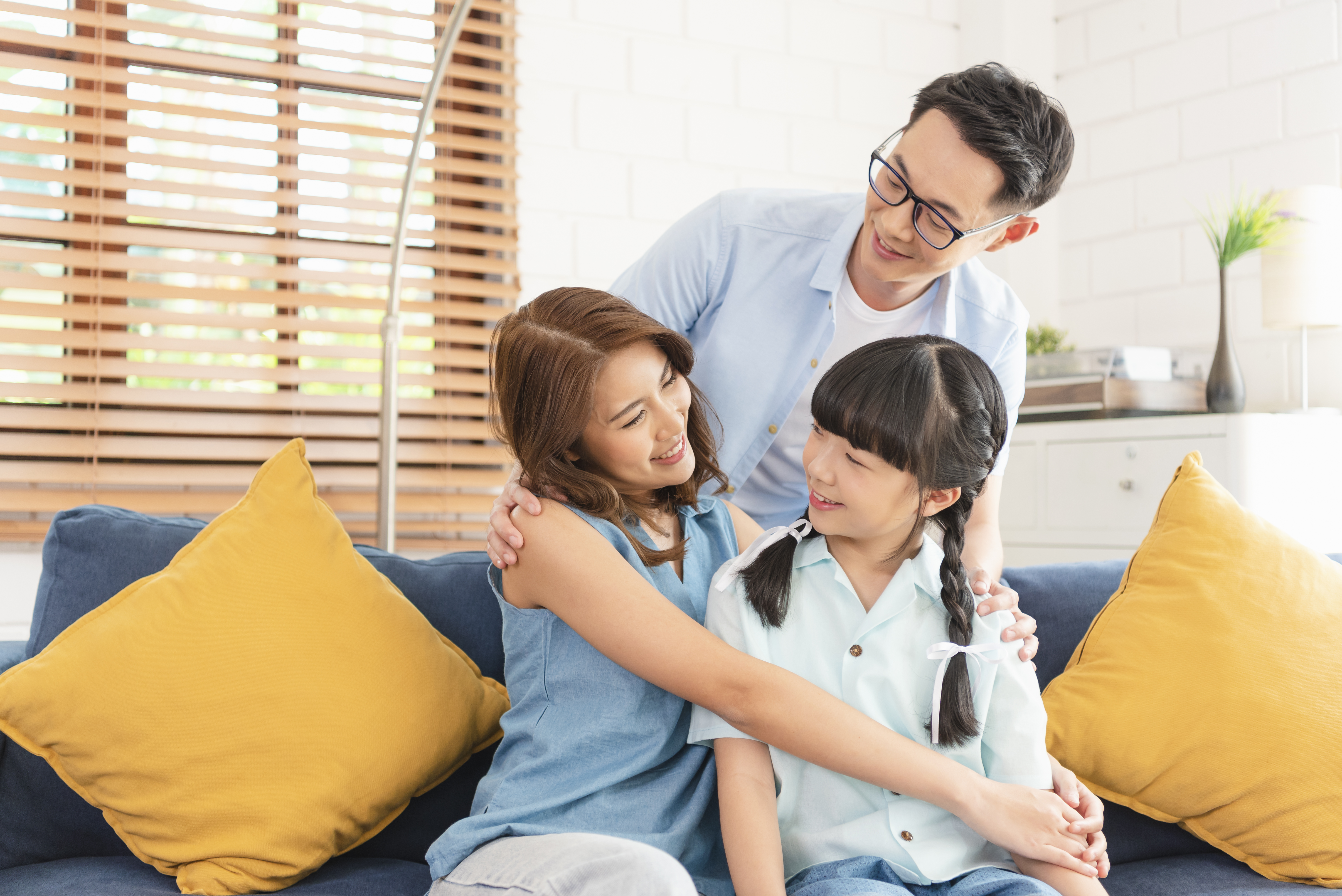 Happy Asian family hugging together on sofa at home living room.